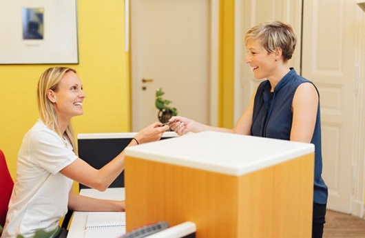 A patient handing her credit card to a dental employee.