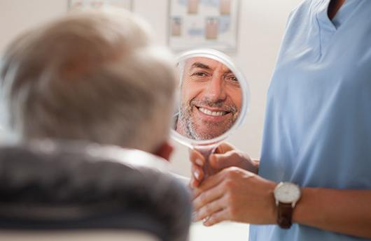 Man looking in mirror during smile makeover appointment