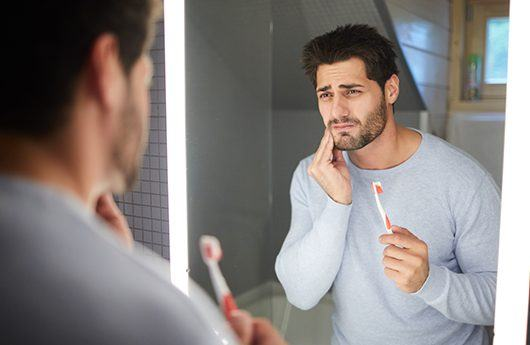 Man in pain while brushing his teeth in need of gum disease treatment