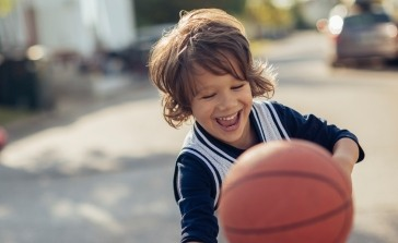 Little boy playing basketball after children's dentistry appointment