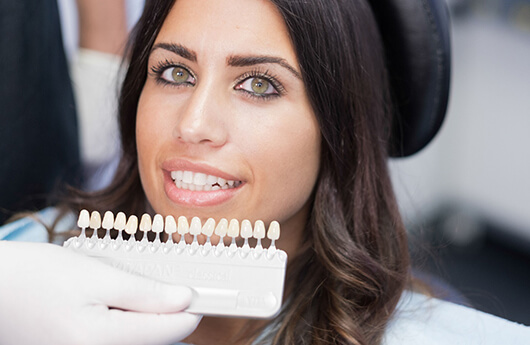 dentist holding veneers in front of woman's face